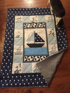 Gorgeous (or handsome!) nautical-themed baby quilt features large hand-designed boat at center with smaller pieced mini sailboats surrounding the feature piece. Backing of fleece, flannel, or cotton, perfect for snuggling your little one!  Custom made to order featuring your nursery colors and pattern preferences - includes private consultation prior to creating your quilt. Size: 48 X 60 final