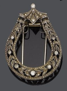 A Belle Époque diamond brooch, circa 1900. The horseshoe millegrain-set with rose, old brilliant, single and brilliant-cut diamonds, the whole capped by a fan and brilliant-cut diamond surmount, converted from a hair ornament.