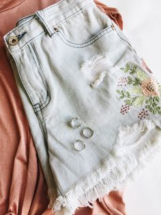 Distressed denim shorts. Raw edge, floral embroidery
