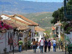 11. Calles de piedra, casas con balcones y techos de teja, vegetación, montañas y personas se mezclan en un solo paisaje