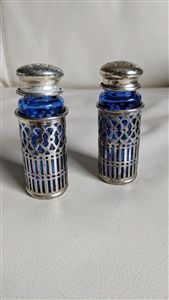 Cobalt blue cage encased salt and pepper shakers. Glass is great, wear to the silvertone encasing and top, one screw top has a line break in it.