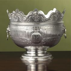 A Queen Anne Silver Monteith, Robert Timbrell & Joseph Bell, London, 1710 the deep bowl with two fluted bands divided by band of inverted bosses against matted ground, both sides chased with cartouches of foliate strapwork, shell and scales and enclosing engraved crests, with ring handles mounted on lion masks and raised on partially fluted foot, the detachable collar with scalloped rim applied with cherub heads flanked by rope-twist scrolls,