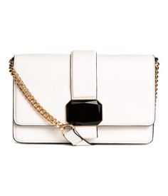Natural white. Shoulder bag in faux leather with decorative stone on flap. Magnetic fastener, narrow shoulder strap with metal chain fasteners, two large