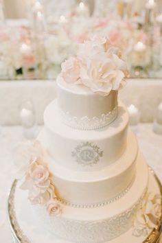 4 tier elegant ivory cake with white detailing and pastel pink flower accents