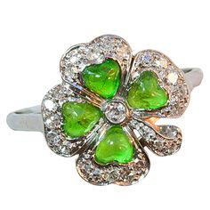 A delicate platinum ring in the shape of a clover set with single cut diamonds and 4 heart shaped cabochon demantoid garnets in the centre of each clover leaf, V.S., circa 1915.