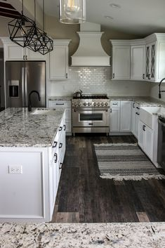 Beautifully elegant white kitchen with gray and black mottled granite and island countertops. The darker wood of the floor really makes the white cabinets, backsplash and countertops stand out.