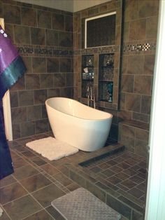 Removal of oversized jetted tub in a tiled base; smaller free-standing soaking tub allowed for expansion of standing shower