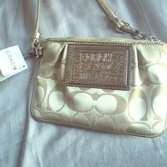 NEW W/ TAGS Gold/Creme Coach wristlet Never used coach wristlet with tags! Creme/beige fabric with gold metallic detail sewn on top near zipper, matches the gold metallic leather strap. Hot pink satin interior. Width approx. 5 1/2 inches Coach Bags Clutches & Wristlets