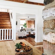 Dream house Wood stairs white walls brick table living room natural light kitchen exposed brick