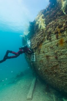 Marc-André Bernier, Parks Canada's manager of underwater archeology, sets a marine biology sampling quadrant on the port side hull of HMS Erebus. (Parks Canada)