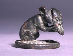 Circular bronze lamp lid with a grip in the form of a crouching mouse holding a Papposeilenos mask. In the rim behind the mouse is a small notch, with the remains of an adjacent rivet.