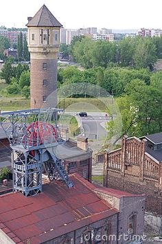 """Aerial view of a closed coal mine """"Katowice"""" in the district of Bogucice. Seen are the shaft """"Bartosz"""", water tower and apartment buildings of Katowice's district Koszutka. Coal Mining, Water Tower, Aerial View, Poland, Buildings, Patio, Stock Photos, History, Architecture"""