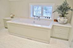 Baderomsinnredning med plasstilpasset speil og lamper på hver side i lys grå farge. Innebygget badekar med møbelfronter og skuffer på sidene. Lekre detaljer med In-frame innredning og knotter i porselen.