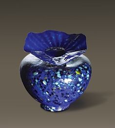 """This is a very graceful piece. The wavy fanning lid sits atop a lovely round globe of rich color. This piece is available in the following colors: angel white with silver accent, blue with silver leaf, yellow, and amethyst with silver leaf.          Dimensions: 9″"""" x 11″     Capacity: 254 cubic inches"""