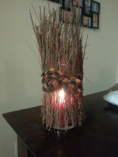Homemade candle decoration with a cinnamon broom cut into smaller sticks and a cut in a half scarf.--Would need to be sure the sticks were low enough that they could not catch fire from the candle inside.