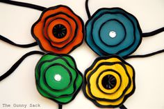 Finally-- an idea of what to do with old leather purses! Cut into graduated circles, paint on a contrasting color, singe with a candle, stack, embellish, then attach to a headband.