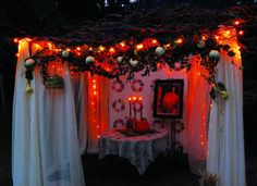 Sukkah made with a portable gazebo, lights, antique quilt, art, willow branches and autumn decor. Lovely for a pleasant Sukkot fall evening.