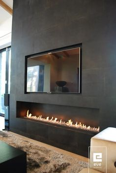 Bellissima parete con incassi per televisione e camino a bioetanolo. Rivestimento in lastre di ceramica di colore nero per un soggiorno moderno di grande classe