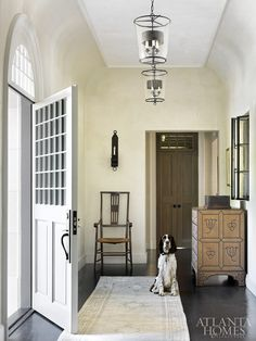 Rounded walls create depth in the entry hall of a Buckhead home by architect Peter Block, interior design Joel Kelly. An antique chair rests beneath an Ainsworth-Noah sconce.