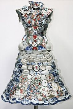 A dress form covered with broken china pieces.