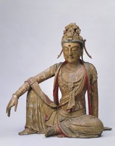 (960-1127)       This statue painted in colour was made with several pieces of wood joined together. This Guanyin (Avalokitesvara) wears a tall coronal with a Buddha's image on top and sautoir hanging down with braids of hair. This image of Guanyin has thin brows, clear eyes, full cheeks and a painted mustache. With the upper part of his body exposed, he wears a long skirt, sautoir on the chest. The clothes and ornaments are sculptured in lively and flowing lines.