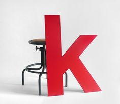 """Large red letter """"k"""" made of wood in a Helvetica font. Great for a unique display piece. Made by Hindsvik on etsy"""