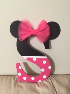 "I bought a black letter ""S"" and painted the bottom half pink with polka dots. Ears made of paper with a tulle bow to top it off. Perfect for a party decoration that can always be made permanent in a bedroom.  Minnie Mouse Letter.."