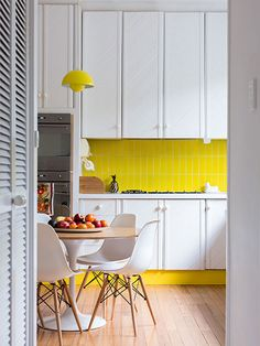 Let a super-bright, vertically installed subway-tile backsplash set the tone for a few surprise hits of color. Here, a pendant light and a painted toekick reinforce the color scheme and provide a cheerful counterpoint to white cabinetry. Try Rittenhouse Square 3-by-6-inch ceramic tile in Sunflower, about $10 per square foot; daltile.com for more information.