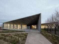 Faceted concrete corridor welcomes children to Taller Básico de Arquitectura's nursery