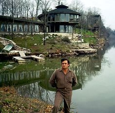 """Johnny Cash at his """"nature house"""" on Old Hickory Lake near Hendersonville. Cash was having a few beers with architect Braxton Dixon at the site and Cash ask """"What in the world is that?"""" Dixon, who built the house for himself, answered """"It's mine."""" Cash said, """"No, it's mine!"""" Staff photo by J.T. Phillips (The Tennessean) 4/19/1969"""