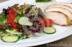 Salad of lettuce, cucumber and tomato with slices of chicken breast
