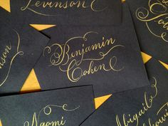 LettersByAnat. Wedding calligraphy, gold ink with pointed pen on black place cards.