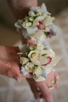 Artography – Wrist corsage with ivory Miniature Roses, mini Cymbidium orchids and silver Dusty Miller