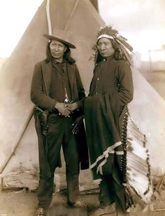 """""""Red Cloud and American Horse."""" The two most noted chiefs of the day. It was created in 1891 by Grabill, John C. H., photographer.  The picture presents Two Oglala chiefs, American Horse (wearing western clothing and gun-in-holster) and Red Cloud (wearing headdress), full-length portrait, facing front, shaking hands in front of tipi--probably on or near Pine Ridge Reservation."""