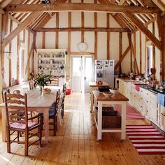 High beam country kitchen.   This magnificent barn kitchen features high wood beams and homely country-style touches. This spacious kitchen design features a great use of natural lighting.