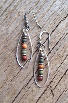 """Hammered silver oval hoops with a small dangle made of natural red creek jasper and antiqued silver. Approx 1.5"""" in length."""