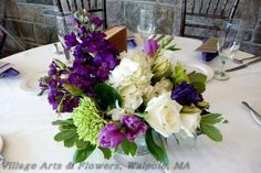 wedding centerpiece of green hydrangea, white roses, purple tulips and purple stock designed by Village Arts & Flowers