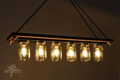 rustic wood mason jar chandelier tutorial - made from a recycled bathroom light fixture attached to a barnwood board.