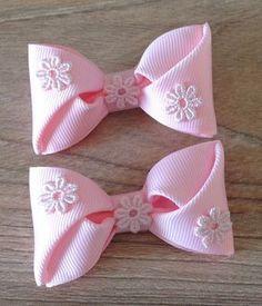 Lacinho em gorgurão importado rosa bebê com aplique de florzinha. 7x3,5 cm aproximadamente. Feito no bico de pato.