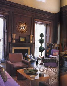 """This is a formal mahogany-paneled living room with lavender chairs and sofa. """"Lavender is the new beige,"""" says Albert Hadley. The chairs facing each other across the original Jean-Michel Frank split-bamboo coffee table exhibit the low horizontal lines and squared cubic surfaces characteristic of Modernism — with the surprise of chocolate brown satin upholstery. Furniture that has an architectural quality is a favorite of Albert Hadley."""