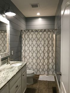 Kids bathroom remodel  (shiplap cut at Lowes, outdoor lights from Lowes, shower curtain from Amazon, mirror made from barn wood and chalk painted)