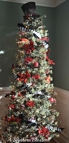 This tree is adorned with red birds, berries and poinsettias along with a simple black snowman's hat.