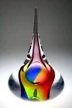 Leerdam glaskunst- Glaskunst gemaakt door meesterglasblazer Gert Bullee en ontworpen door Patrick de Keijzer. Het object staat op een brede basis van waaruit een kleurrijke kern stroomt. De kleuren zijn prachtig zichtbaar door de dikke laag transparant glas. De natuurlijke vormgeving in combinatie met het fascinerende kleurenspel maken dit object tot een lust voor het oog! De hoogte van het object is 34cm.