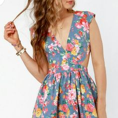 """Foral Dress Cutout Floral Print Dress pulls from the best with its pink floral print over a stretchy denim blue twill. Padded shoulders lead into a sexy, deep V neckline framed by angular open side cutouts, and a banded waist breaks into a full skirt with layers of tulle underneath for extra """"poof""""! Hidden back zipper/hook clasp. Skirt is lined. Shell: 60% Cotton, 40% Polyeste Dresses Mini"""