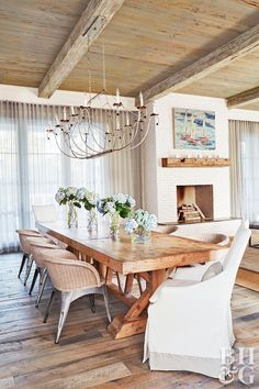 The dining area's large farmhouse table seats up to 10 people, emphasizing the w. The dining area's large farmhouse table seats up to 10 people, emphasizing the way the home celeb Farmhouse Dining Room Table, Dining Room Furniture, Wicker Dining Room Chairs, Rustic Table, Large Dining Room Table, Large Table, White Oak Dining Table, Dining Room Fireplace, Wicker Table