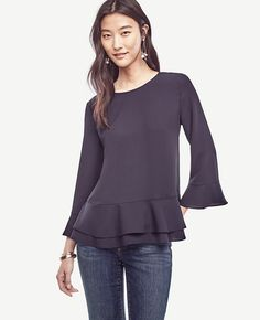 "Embrace softer silhouettes with bits of feminine flounce, like this fluid woven piece mixed with soft matte jersey. Jewel neck. 3/4 sleeves with flounce cuffs. Double flounce hem. Back slit with hook-and-eye closure. 26 1/2"" long."