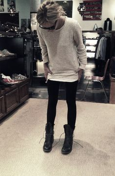 black leggings, black clunky open combat boots, oversized light colored sweater, and black sunglasses.