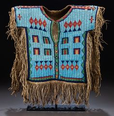 A SIOUX BOY'S PICTORIAL BEADED AND FRINGED HIDE SHIRT. c. 1875