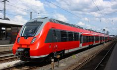 Photo about A red train in a railway-station (train-station) waiting for passengers. Image of modern, carriage, travel - 36488203