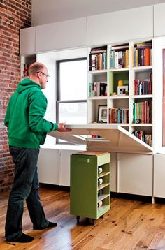// 2010, Dwell showcased a wall hiding a bookshelf that folded down to create a table set atop a rolling island.  I think think that there is a ledge on the roling top that is the size of the display cut out on the shelf cover.  I want these rbery where in my house